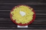 Шаг 3. На плоскую тарелку первым слоем выложить натертый отварной картофель
