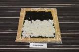 Шаг 3. На 2/3 листа нори выложить рис, свободный край слегка смочить водой.