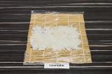 Шаг 4. Лист нори разрезать пополам, по всей площади листа плотным слоем выложить