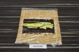 Шаг 5. Перевернуть лист нори рисом вниз, выложить начинку: сыр фета, огурец