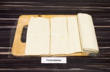 Шаг 1. Тесто полностью разморозить, развернуть пласт и нарезать 10 полосок.