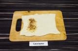 Шаг 2. Растянуть полоску в прямоугольник, выложить сыр, натертый на терке, и спе