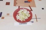 Шаг 3. Лук измельчить и выложить на раскаленную сковороду, смазанную кукурузным