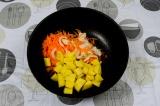 Шаг 6. Добавить лук, морковь и манго. Пассеровать 5-7 минут.