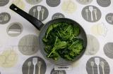 Шаг 2. Шпинат завялить на сухой сковороде с добавлением соли и воды.