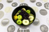 Шаг 3. В кастрюлю влить воду, добавить фрукты, базилик, мяту и эритритол. Варить