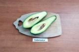 Шаг 1. Авокадо помыть, разрезать на 2 части и вынуть косточку.