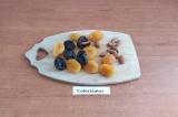 Шаг 1. Сухофрукты помыть, обсушить, в каждом сделать надрез и вложить по 1 ореху
