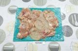 Шаг 5. Застелить доску или стол пищевой пленкой и выложить отбитое мясо тонким
