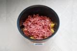 Шаг 4. В чашу мультиварки положить лук, морковь, картофель, фарш, посолить.