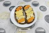Шаг 5. Выложить разные сорта сыра на каждый ломтик хлеба. Запечь в микроволновке