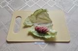 Шаг 4. На лист капусты выложить немного фарша и завернуть.