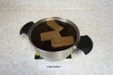 Шаг 2. Изюм хорошо промыть. В кастрюлю с водой вылить солодовый раствор, добавит