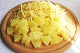 Шаг 2. Ананас порезать кубиками и натереть сыр на терке.