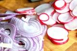 Шаг 2. Тонкими пластинками нарезать редиску. Нарезать лук полукольцами.