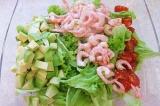 Шаг 6. Смешать огурцы, помидоры, креветки и авокадо. И выложить на листья салата