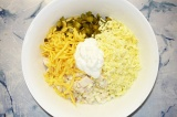 Шаг 6. Перемешать грудку, лук, огурцы, желтки и половину тертого сыра, заправить