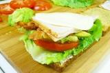 Шаг 4. На хлеб с майонезом уложить лист капусты, бекон, кружочки помидора, индей