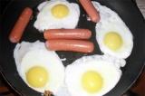 Шаг 2. В сковороде обжарить яйца и сосиски. На каждый ломтик обжаренного хлеба