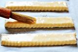 Шаг 6. Выложить сырные палочки на противень и смазать взбитым яйцом.