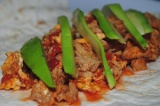 Шаг 10. На тортилью выложить посередине приготовленную начинку и кусочки авокадо