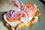 Шаг 6. На мясо положить пару ломтиков помидора и красный лук.