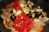 Шаг 5. Добавить баклажаны, лук и помидоры. В конце добавить чеснок, посолить.