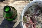 Шаг 4. Выложить лук к мясу, добавить специи, чеснок, залить пивом и перемешать.