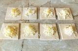 Шаг 4. В серединку каждого квадрата добавить тертый сыр и кусочек масла.