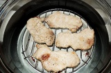 Шаг 3. Уложить отбивные на среднюю решетку аэрогриля, готовить 15 минут.