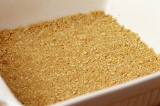 Шаг 4. Форму смазать маслом и на дно выложить измельченное печенье.