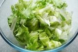 Шаг 4. Салат «айсберг» разделить на листья и мелко порвать их руками. Уложить