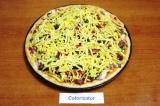 Шаг 8. Сыр натереть на терке и посыпать им пиццу.