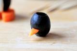 Шаг 5. В маленькой оливке сделать небольшой надрез и вставить морковный треуголь