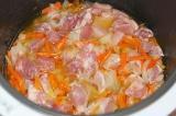 Шаг 4. Мясо нарезать небольшими кусочками и добавить в плов с водой. Включить ре