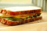 Шаг 4. Уложить кусочки авокадо, сыр. Сверху уложить еще один ломтик хлеба. Обжар