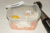 Шаг 2. Выложить морковь, лук, чеснок в миску, добавить яйцо, муку, соль, перец и