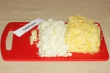 Шаг 2. Кабачок натереть на крупной терке; лук нарезать кубиками; чеснок натереть
