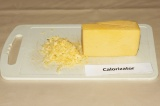 Шаг 6. Пока паста тушится, натереть сыр на крупной терке.