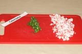 Шаг 1. Крабовые палочки и зеленый лук мелко нарезать.