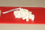 Шаг 6. Пока сливки с грибами варятся, нарезать кубиками плавленый сыр.
