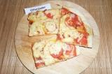 Готовое блюдо: пицца с ветчиной и томатами