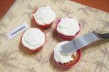 Шаг 8. Взять ножом-лопаткой шарик крема и намазать кекс сверху от центра к краю.
