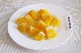 Шаг 6. Очистить апельсин от кожуры и тоже нарезать крупными дольками.