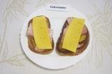 Шаг 6. Положить на поджаренный хлеб по два кусочка ветчины и накрыть полоской сы