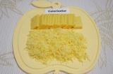 Шаг 1. Разделить брусочек сыра пополам. Одну половину натереть на мелкой терке
