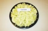 Шаг 3. Выложить ломтики яблока и лука вперемешку в плоскую форму. Полить лимонны