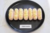 Шаг 4. Выложить сосиски на противень, посыпать их красным перцем. Разогреть духо