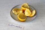 Шаг 1. Нарезать крупными дольками лимон. В чайник слегка выдавить сок и положить