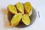 Шаг 6. Кусочки багета намазать смесью оливкового масла с чесноком (с двух сторон